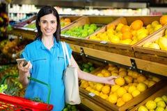 Portrait of a smiling woman picking orange Stock Photos