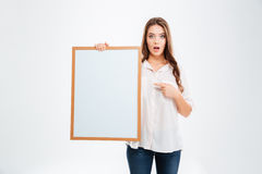Portrait of a smiling woman pointing finger on blank board Royalty Free Stock Photos