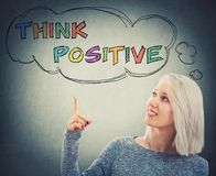 Think positive. Portrait of smiling woman pointing her finger up to a thought bouble with the text think positive. Colorful motivatinal slogan, having fun, enjoy royalty free stock photography