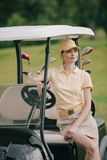 portrait of smiling woman in polo and cap sitting on golf cart