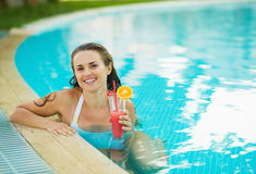 Portrait of smiling woman at pool with cocktail Stock Image