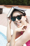 Portrait of smiling woman by the pool in sunglasses holding a book over her head Stock Photo