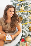 Portrait of smiling woman and postcard near christmas tree Stock Images