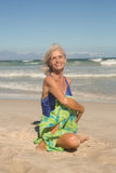 Portrait of smiling woman practising yoga while sitting on sand Stock Photography