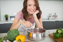 Portrait of smiling woman preparing food in kitchen Stock Image
