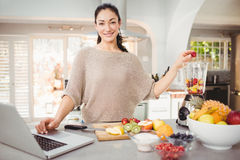 Portrait of smiling woman preparing fruit juice while working on laptop Royalty Free Stock Photography