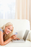 Portrait of a smiling woman purchasing online stock photos