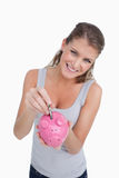 Portrait of a smiling woman putting a note in a piggy bank Royalty Free Stock Photo