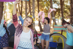 Portrait of smiling woman raising hand with friends in background Stock Photos