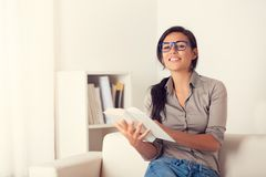 Woman reading a book on couch at home Stock Images