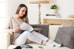 Smiling woman reading a magazine on a couch. Portrait of smiling woman reading a magazine on a couch at home royalty free stock photography