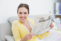 Portrait of a smiling woman reading newspaper at home Stock Images
