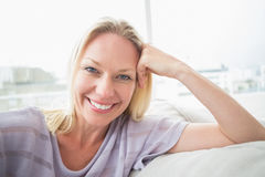 Portrait of smiling woman relaxing on sofa Royalty Free Stock Photo