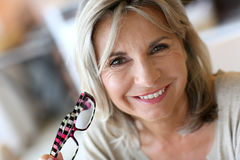 Portrait of smiling woman removing eyeglasses royalty free stock photography
