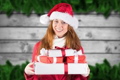 Portrait of smiling woman in santa costume holding christmas gifts. During christmas time Stock Photo