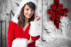 Portrait of smiling woman in santa costume. Standing against digitally generated background Stock Photography