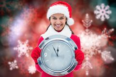Portrait of smiling woman in santa hat holding clock against digitally generated background Stock Images