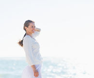 Portrait of smiling woman on sea shore looking into distance Royalty Free Stock Photos