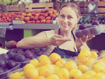 Portrait of smiling woman selling ripe fresh plums Royalty Free Stock Photography