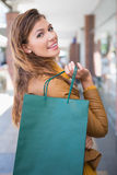Portrait of smiling woman with shopping bag looking at camera Stock Photos