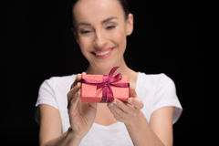 Portrait of smiling woman showing gift on black, focus on foreground. International womens day concept Royalty Free Stock Photo