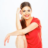 Portrait of smiling woman sitting against white background. Royalty Free Stock Photography