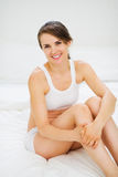 Portrait of smiling woman sitting on bed Royalty Free Stock Photos