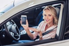 Woman in teh car showing smartphone stock photography