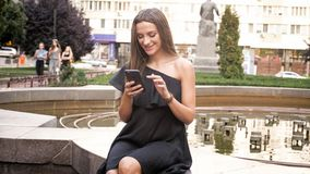 Portrait of beautiful smiling woman sitting at fountaing and using mobile phone stock photos