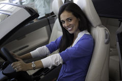 Portrait of smiling woman sitting in front seat of car stock photo