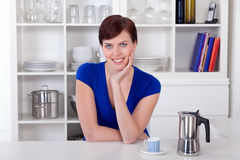 Miling woman sitting in her kitchen with a coffee moka pot Royalty Free Stock Photo