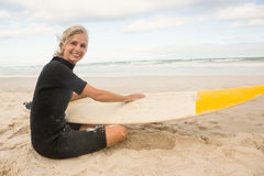 Portrait of smiling woman sitting with surfboard against sky stock photos
