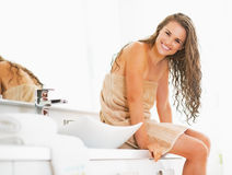 Portrait of smiling woman sitting with wet hair in bathroom Stock Photos
