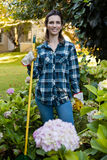 Portrait of smiling woman standing with gardening equipment by hydrangea flowers Stock Images
