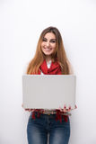 Portrait of a smiling woman standing with laptop Stock Photo