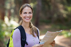 Portrait of smiling woman standing with map Royalty Free Stock Photo