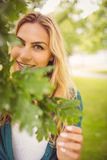 Portrait of smiling woman standing by tree at park Royalty Free Stock Image