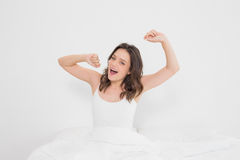 Portrait of a smiling woman stretching her arms in bed Stock Photography