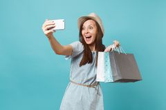 Portrait smiling woman in summer dress, straw hat holding packages bags with purchases after shopping doing selfie shot. Portrait smiling woman in summer dress royalty free stock images