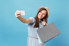 Portrait smiling woman in summer dress, straw hat holding packages bags with purchases after shopping doing selfie shot. Portrait smiling woman in summer dress royalty free stock photography