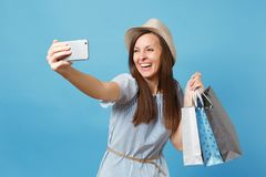 Portrait smiling woman in summer dress, straw hat holding packages bags with purchases after shopping doing selfie shot. Portrait smiling woman in summer dress stock photo