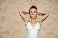 Portrait of smiling woman in swimsuit laying on the sand Royalty Free Stock Images