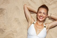 Portrait of smiling woman in swimsuit laying on the sand. Warm sand treatment. Portrait of smiling woman in swimsuit laying on the sand Stock Images