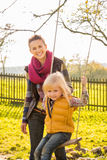 Portrait of smiling woman and swinging child in autumn outdoors Royalty Free Stock Photography