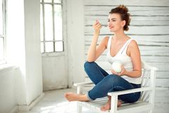 Healthy Lifestyle. Portrait Of Smiling Woman Tasting Fresh Organic Yogurt sitting in white bright room, wearing in white Royalty Free Stock Photo