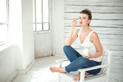 Healthy Lifestyle. Portrait Of Smiling Woman Tasting Fresh Organic Yogurt sitting in white bright room, wearing in white Stock Photography