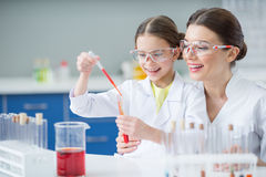 Portrait of smiling woman teacher and girl student scientists making experiment Stock Photography