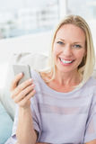Portrait of smiling woman text messaging through smart phone Royalty Free Stock Image