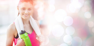 Portrait of smiling woman with towel and bottle. Portrait of smiling women with towel and bottle at gym Stock Images