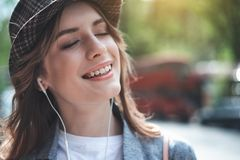 Pretty young lady is listening to music with grin. Portrait of smiling woman in trendy hat enjoying some audios oute. She has eyes closed while using headphones royalty free stock images
